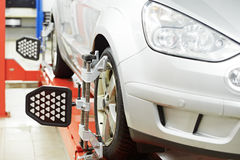 Car at wheel alignment diagnostic tester. Automobile car during wheel alignment and wheel camber at diagnostic tester in repair service station Royalty Free Stock Photos