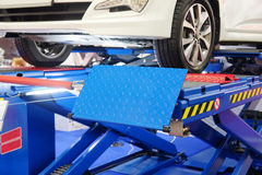 Car on a wheel alignment lift. Image of a Car on a wheel alignment lift Stock Photo
