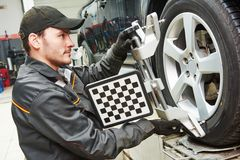 Car wheel alignment service work. Car mechanic installing sensor during suspension adjustment and automobile wheel alignment work at repair service station Royalty Free Stock Photography