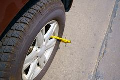 Car wheel blocked by wheel lock. Because illegal parking violation Stock Photos