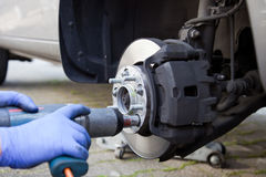 Car wheel changed by mechanic. Auto mechanic changing wheel on car with pneumatic wrench Stock Images