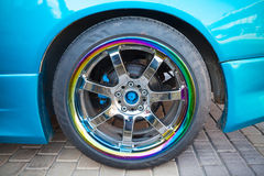 Car wheel on colorful metallic disc, close up photo Royalty Free Stock Photos