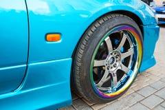 Car wheel on colorful metallic disc, closeup photo Stock Photography