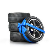 Car Wheel enveloped in a blue ribbon and bow Royalty Free Stock Images