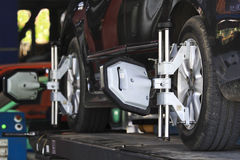 Car wheel fixed with computerized wheel alignment machine clamp.  Royalty Free Stock Image