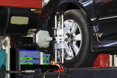 Car wheel fixed with computerized wheel alignment machine clamp.  Royalty Free Stock Photos