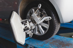 Car wheel fixed with computerized wheel alignment machine clamp Stock Photos
