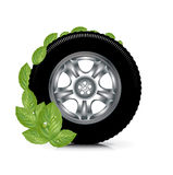 Car wheel and green leaves; green energy concept isolated Royalty Free Stock Photos