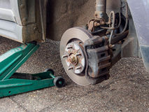 Car wheel hub detail tyre removed. Car on jack with wheel removed showing brake discs Stock Photos