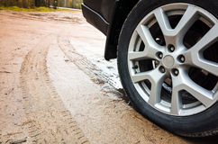Car wheel with light alloy disc on dirty country road Royalty Free Stock Image