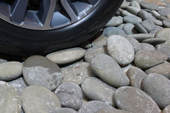 Car wheel on pebbles Royalty Free Stock Photos