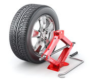 Car wheel with red scissor jack Stock Image