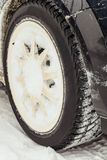 Car wheel with snowy winter tire. Car tyre for winter Royalty Free Stock Photo