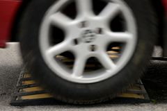 Car wheel and speed bumps closeup. Image of car wheel and speed bumps closeup stock photography