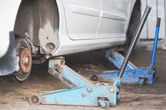 Car wheel tire replacement on tire jack Royalty Free Stock Photo