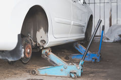 Car wheel tire replacement on tire jack Stock Photo