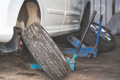 Car wheel tire replacement on tire jack Royalty Free Stock Image