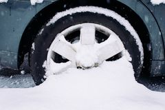 Car wheel with winter tires in the snow. Wheel stuck in a snowdrift. Snow drifts on road, bad weather stock image