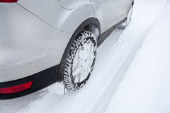 Car wheel in winter tyre driving on snow, close up Stock Photo
