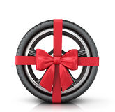 Car wheel wrap a red ribbon with a bow. On a white background Stock Photos