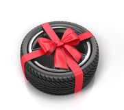 Car wheel wrap a red ribbon with a bow. On a white background Royalty Free Stock Images