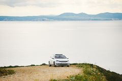 A car of white color, the station wagon travels along a dirt road, stony roads along the coastline in the mountains near the coast. Of the Costa Brava of the Stock Photo