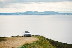 A car of white color, the station wagon travels along a dirt road, stony roads along the coastline in the mountains near the coast. Of the Costa Brava of the Royalty Free Stock Images