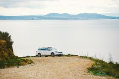 A car of white color, the station wagon travels along a dirt road, stony roads along the coastline in the mountains near the coast. Of the Costa Brava of the Stock Image