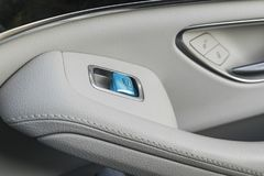 Car white leather interior details of door handle with windows controls and adjustments. Car window controls blue button of modern Royalty Free Stock Images