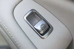 Car white leather interior details of door handle with windows controls and adjustments. Car window controls of modern car Stock Image