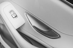 Car white leather interior details of door handle with windows controls and adjustments. Car window controls of modern car. Car de. Tailing. Black and white royalty free stock photography