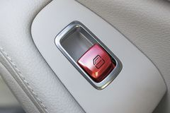 Car white leather interior details of door handle with windows controls and adjustments. Car window controls red button of modern Royalty Free Stock Photo
