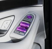 Car white leather interior details of door handle with windows controls and adjustments. Car window controls of modern car Stock Images