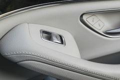 Car white leather interior details of door handle with windows controls and adjustments. Car window controls of modern car Stock Photos