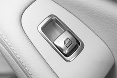 Car white leather interior details of door handle with windows controls and adjustments. Car window controls of modern car. Car de. Tailing. Black and white Stock Photos