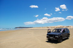 Car at white sand beach Stock Photos
