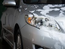 The car with white soap on the body in car care shop. Car wash c. Oncept Stock Photos