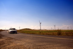 Car through the Wind mill far land Royalty Free Stock Photography