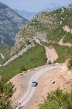 Car, Winding Road And Albanian Mountains. Car is traveling uphill the winding dirt road between the albanian mountains down into the Kelmend Valley royalty free stock photography