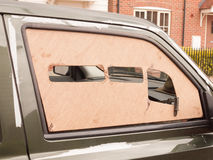 A car window boarded up with wood panel outside Stock Images