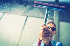 Car Window Cleaning. Caucasian Men Removing Water From His Car Window Right After Washing. Vehicle Window Cleaning Theme stock image