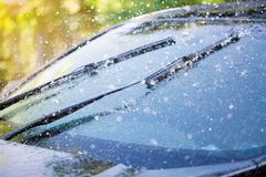Car windshield with rain drops and frameless wiper blade stock photos
