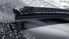 Car windshield with rain drops and frameless wiper blade closeup Stock Photography
