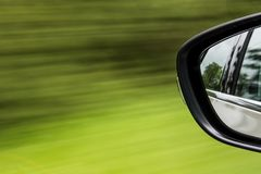 Car wing mirror abstract zooming past grass road. Car wing mirror abstract zooming past grass by the e of the road Stock Photos