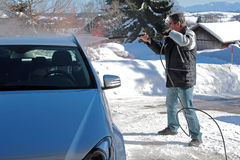 Car in winter. A man washes a car in winter royalty free stock images