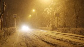 Car on winter road in blizzard, traffic on a city snowy street at night, pedestrian crossing sign stock footage