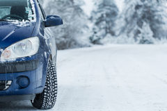 Car on winter road with forest in background. Stock Image