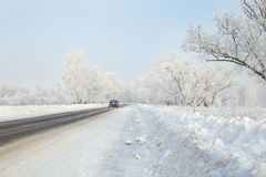 Car on a winter road in the woods leaving afar Stock Images