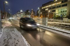 Car in winter with sidwalk, and blurred car light Royalty Free Stock Photo