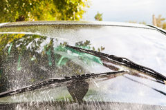Car wipers wash windshield. Outdoor view of auto wipers wash windshield when driving in rain Stock Photos